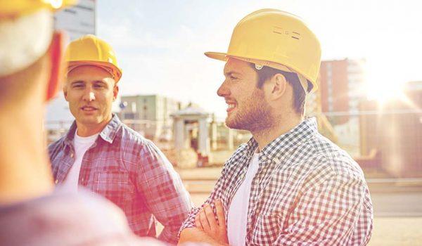 Mannen communiceren op de bouwplaats