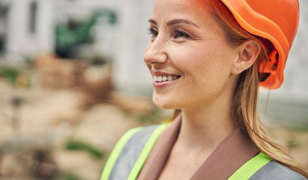 Vrouw met helm in de bouw lacht