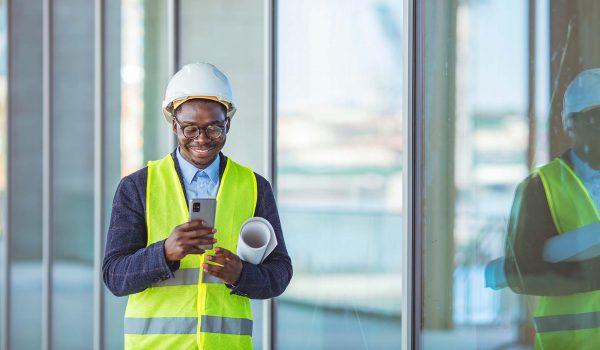 Man kijkt op zijn telefoon op de bouwplaats