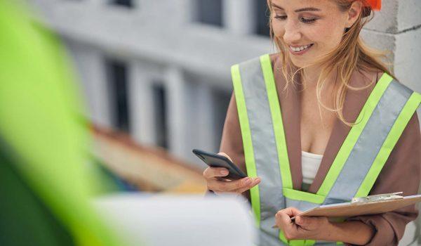 Vrouw in de bouw speelt spel op haar telefoon