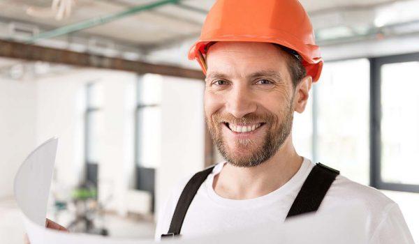 Man met oranje helm uit de bouw lacht